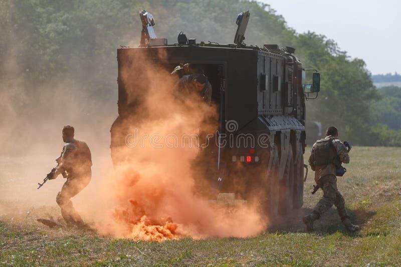 Varios combatientes rusos de las fuerzas especiales desembarcan de un vehículo ligero blindado en el humo que defiende anaranjado fotografía de archivo libre de regalías