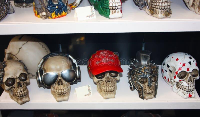 Varios cráneos plásticos falsos disfrazados con los accesorios lindos y divertidos arreglaron en un estante alineado en venta fotos de archivo libres de regalías