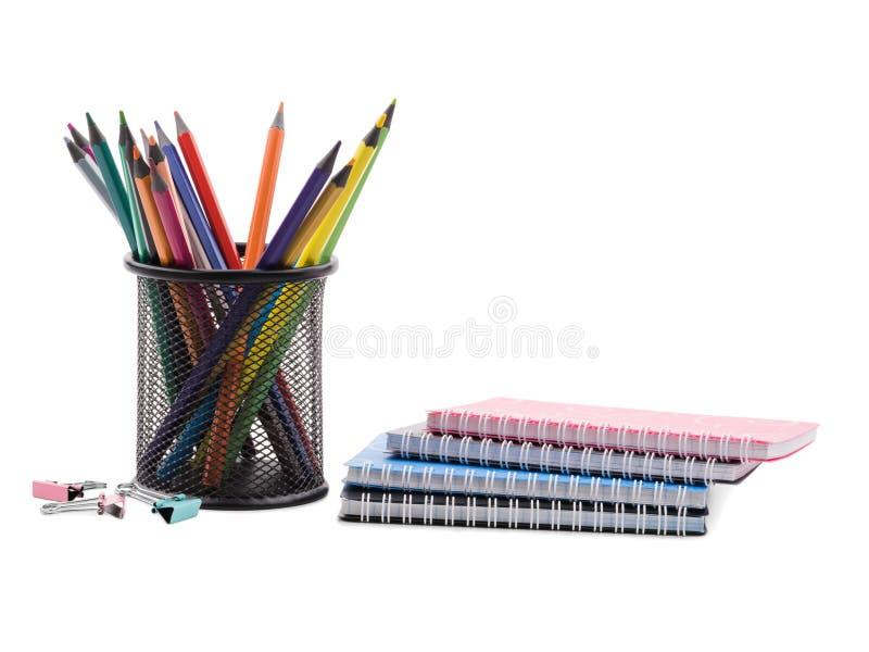 Varios cuadernos y lápices coloreados en una taza y varios clips para los papeles El concepto de educación imagen de archivo