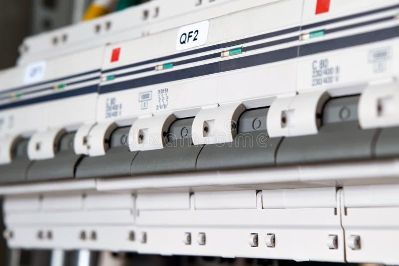 Varios disyuntores modulares están situados en una gama en un gabinete eléctrico imágenes de archivo libres de regalías