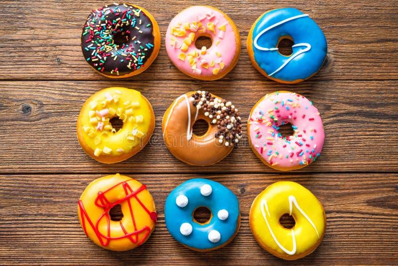 Varios donuts coloridos sobre madera imagen de archivo libre de regalías
