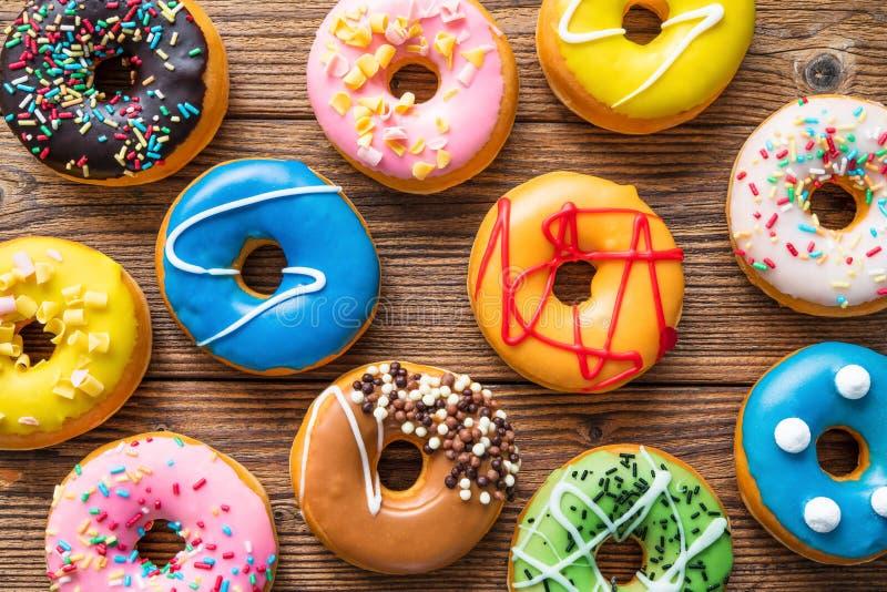 Varios donuts coloridos sobre madera fotografía de archivo