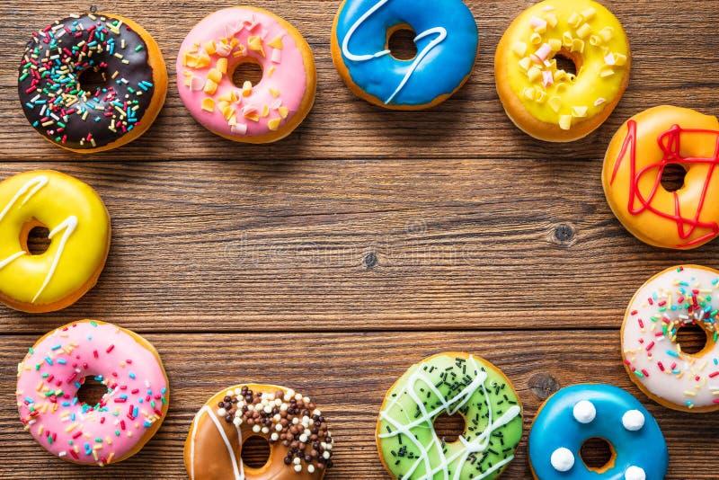 Varios donuts coloridos sobre madera foto de archivo