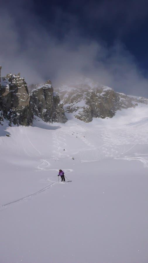 Varios esquiadores backcountry disfrutan de una pendiente del esquí abajo de un pico remoto del moutain en Suiza en un día de inv imagen de archivo