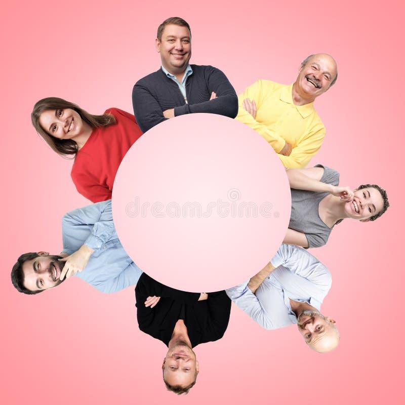 Varios hombres y mujeres europeos positivos sonrientes en círculo sobre backgrpund rosado imágenes de archivo libres de regalías