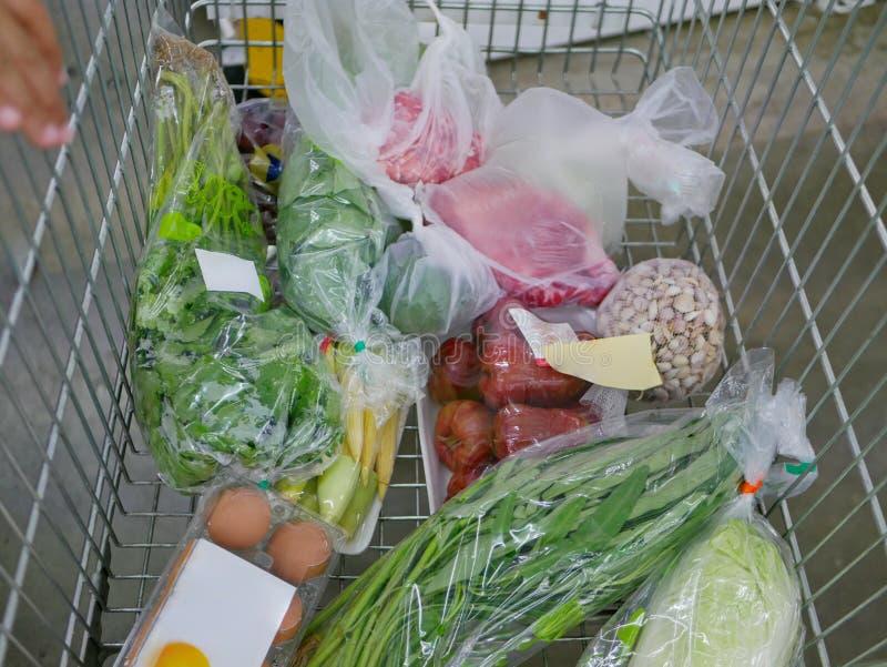 Varios ingredientes alimentarios crudos, en un carro de la compra, siendo comprado en un supermercado foto de archivo