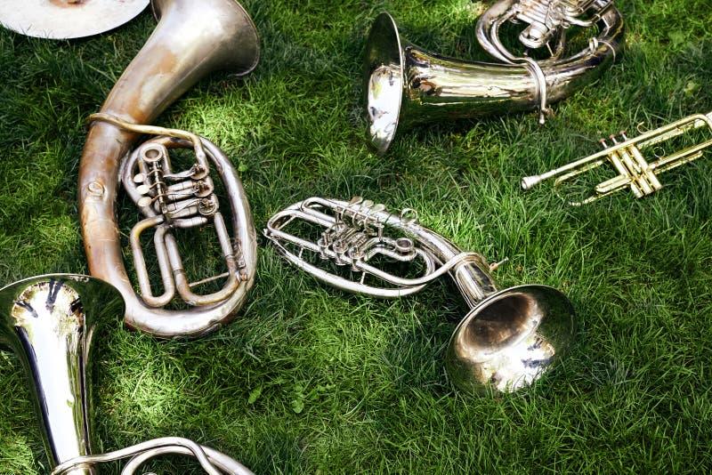 Varios instrumentoes de viento musicales antiguos mienten en la hierba verde imágenes de archivo libres de regalías