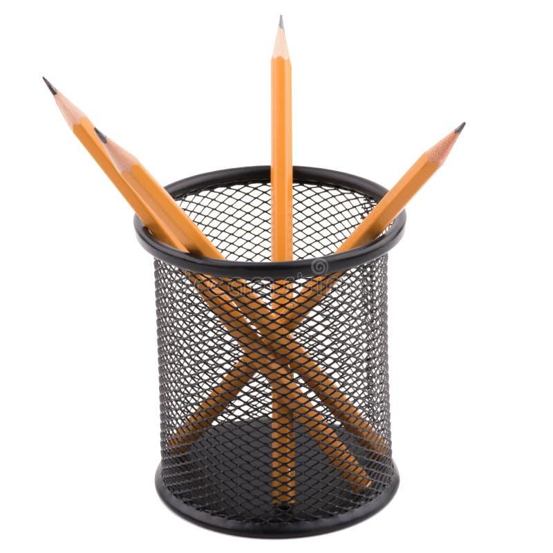 Varios lápices están dentro de una taza negra Aislamiento en un teléfono blanco foto de archivo