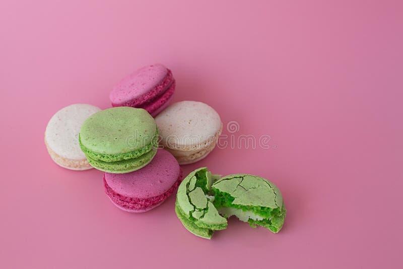 Varios macarons multicolores en un fondo rosado imágenes de archivo libres de regalías