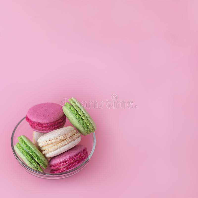 Varios macarons multicolores en una placa de cristal en un fondo rosado cuadrado fotos de archivo
