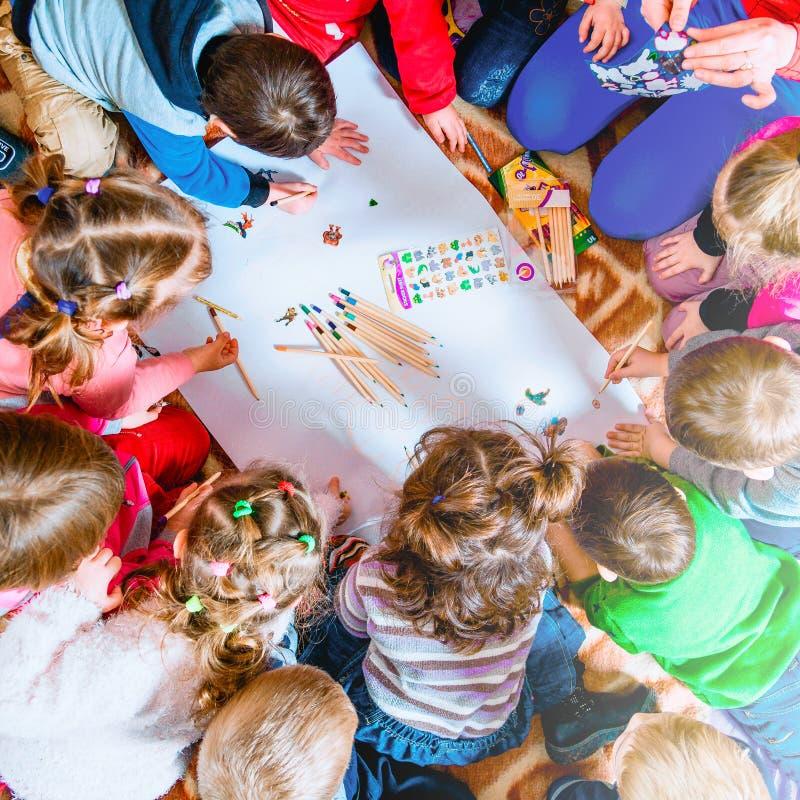Varios pequeños niños dibujan en una hoja de papel con los lápices Una visión desde arriba fotografía de archivo libre de regalías