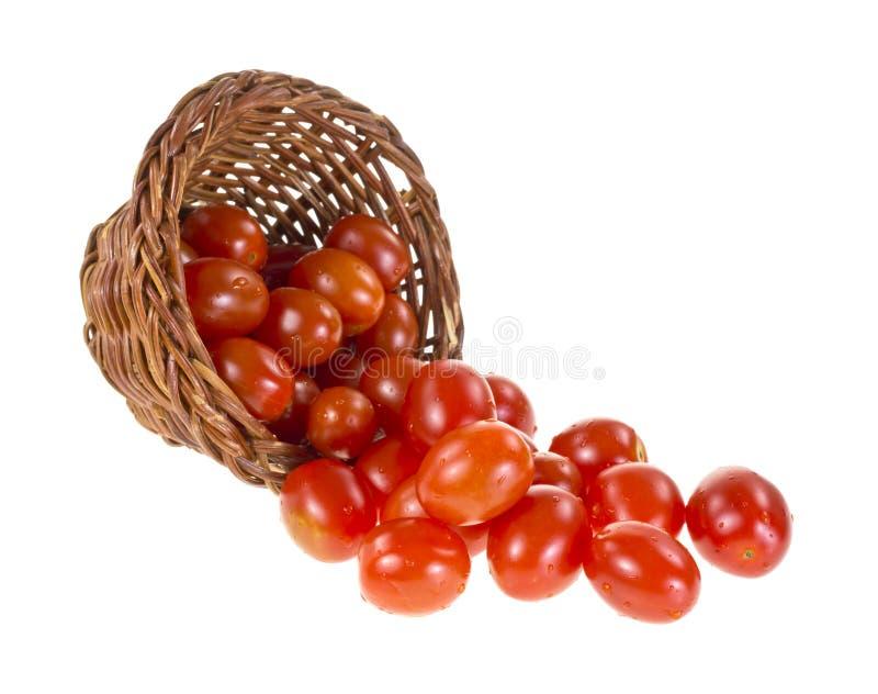 Tomates de la uva que desbordan la cesta fotografía de archivo
