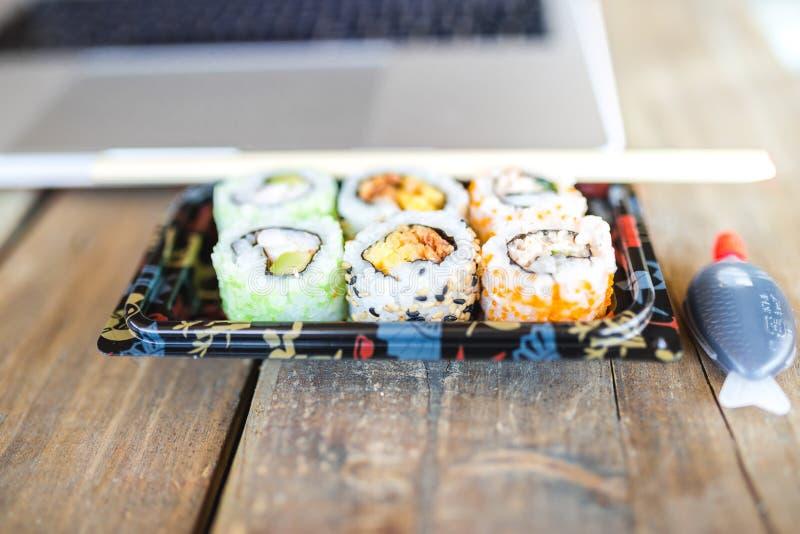 Varios rollos de sushi sabrosos y ordenador portátil en la tabla de madera foto de archivo