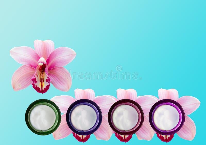 Varios tarros de crema y de orquídeas de cara imagenes de archivo