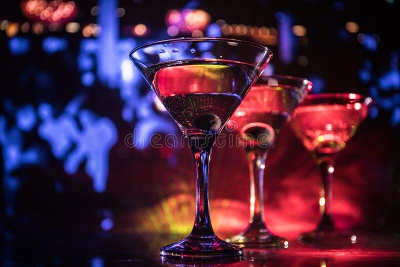Varios vidrios del cóctel famoso Martini, tiro en una barra con las luces de niebla entonadas oscuras del fondo y del disco Conce fotos de archivo
