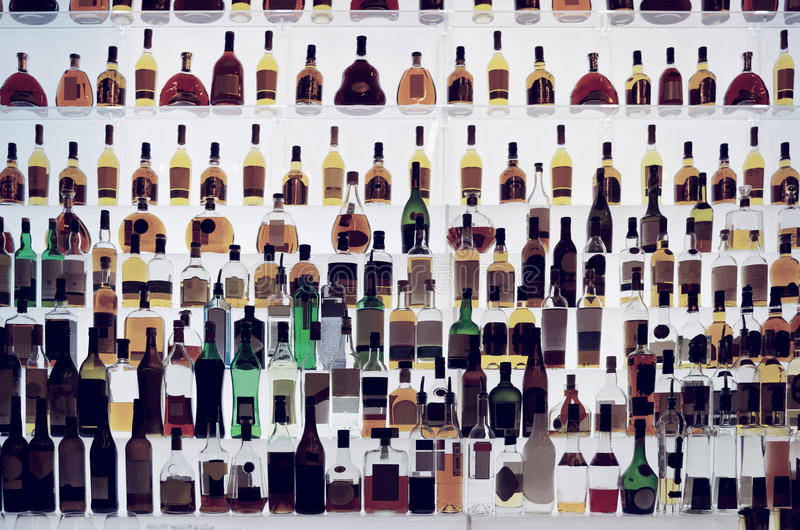 Various alcohol bottles in a bar, toned royalty free stock photos