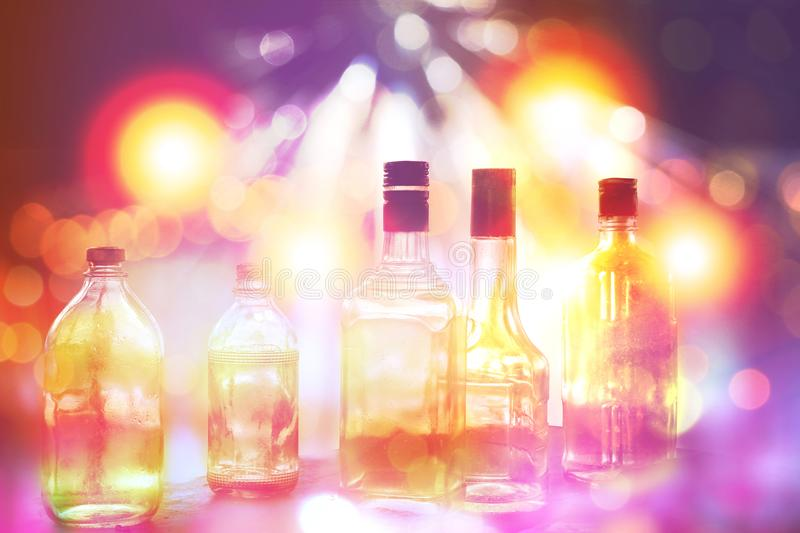 Various alcohol bottles in party with colourful light stock images
