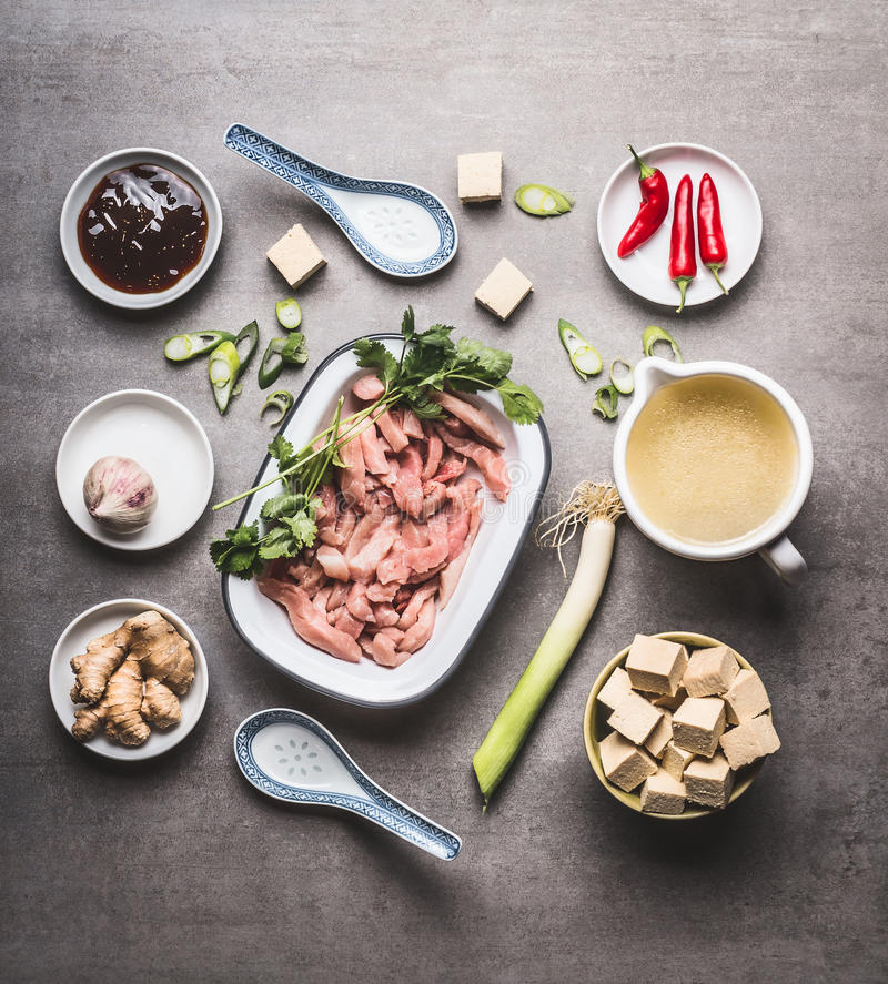 Various asian cooking ingredients in bowls for spicy asian soup with tofu and meat : sliced meat, ginger, chili, diced tofu ,Oyst stock photography