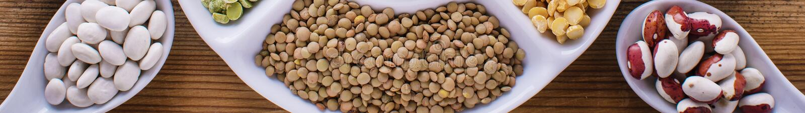 Various assortment of legumes - beans, soy beans, chickpeas, lentils, green peas. Top view banner format royalty free stock image