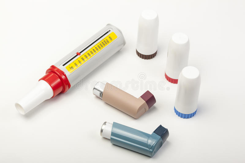 Various asthma inhalers and a peek low meter on white. Various types of spray and powder asthma inhalers and a peek low meter on a white background royalty free stock photos