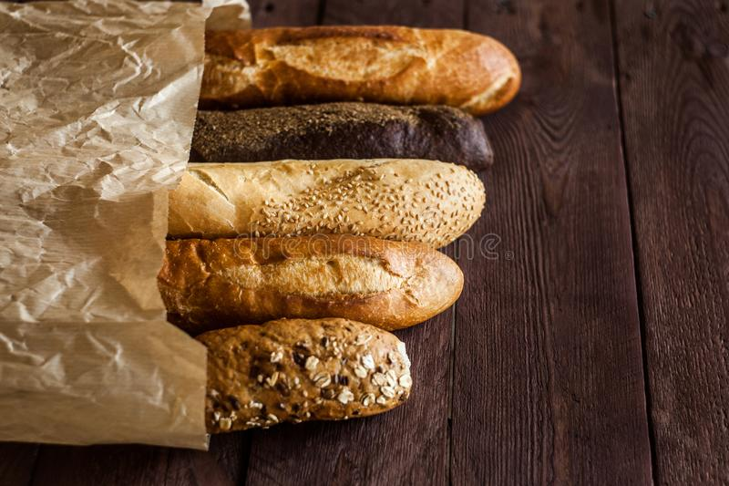 Various baked breads and baguettes on rustic wooden table. Close up royalty free stock photo