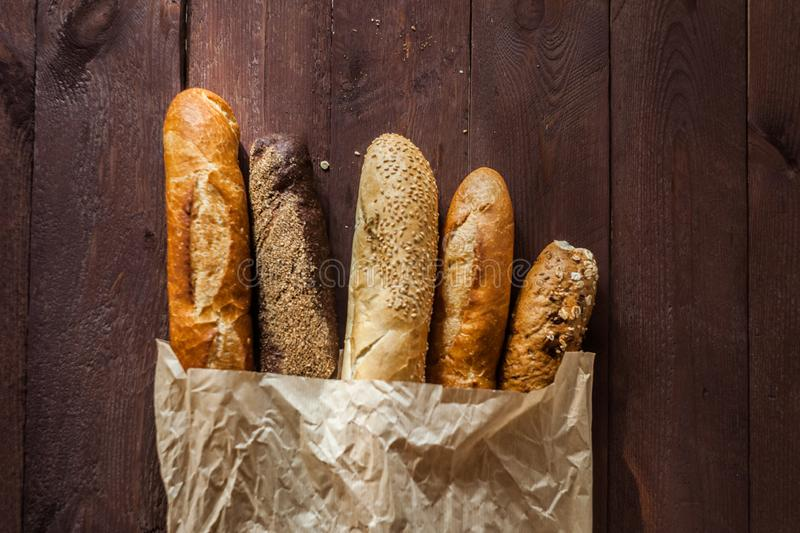 Various baked breads and baguettes on rustic wooden table. Close up stock image