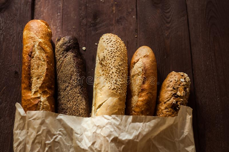 Various baked breads and baguettes on rustic wooden table. Close up royalty free stock image
