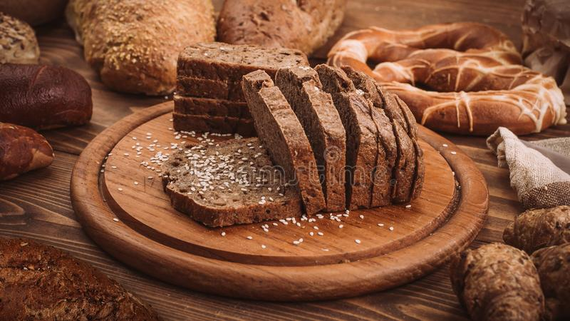 Various baked breads and rolls on rustic wooden table stock photo