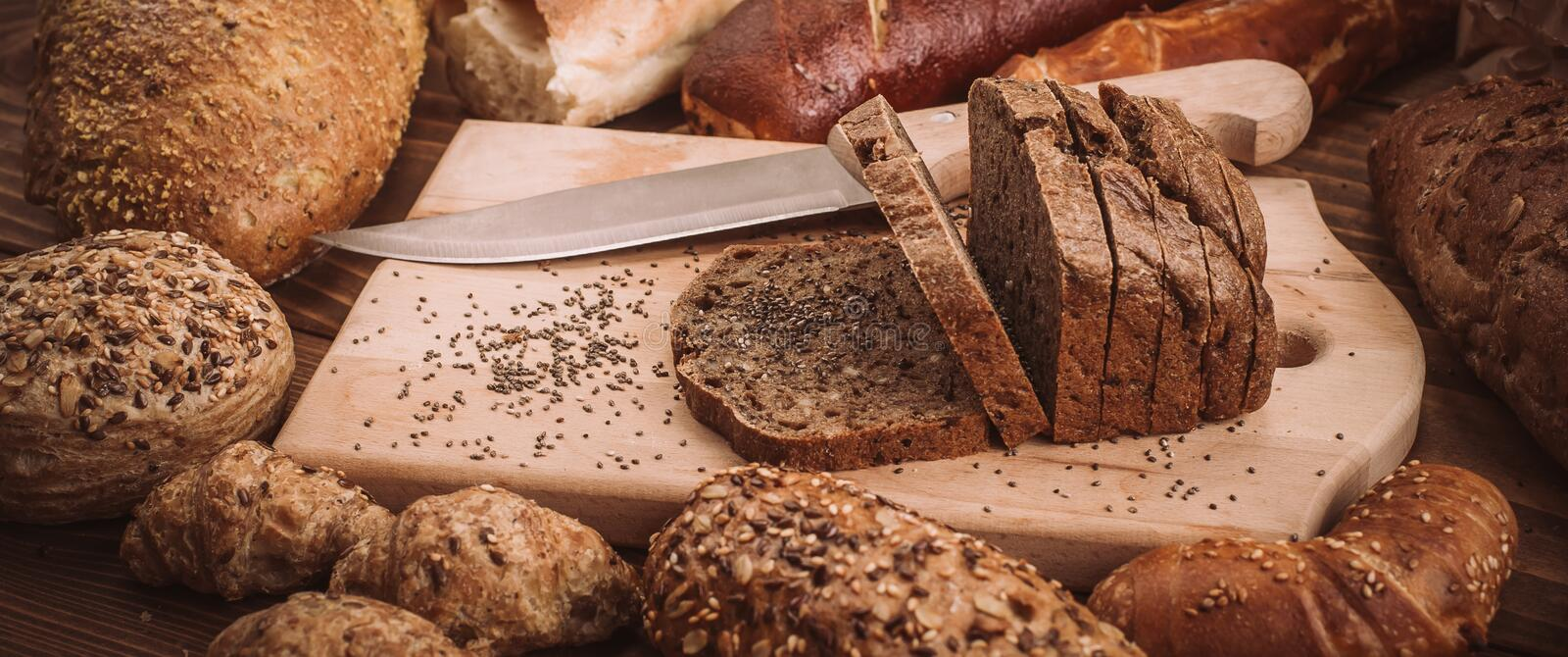 Various baked breads and rolls on rustic wooden table stock image