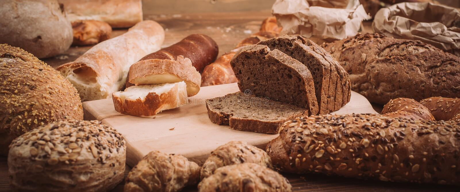 Various baked breads and rolls on rustic wooden table royalty free stock photography