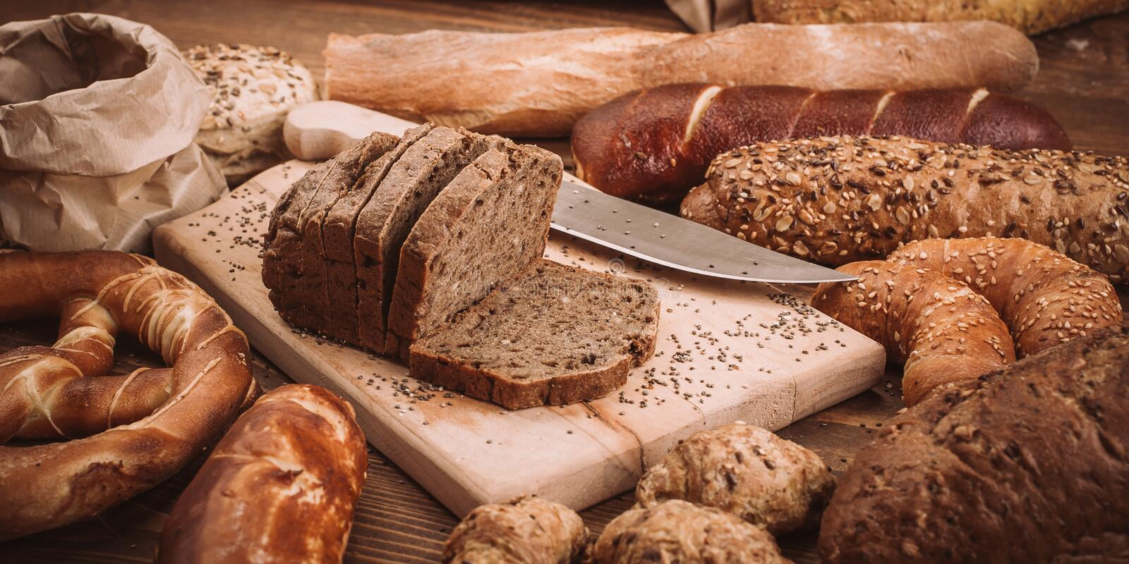 Various baked breads and rolls on rustic wooden table royalty free stock image