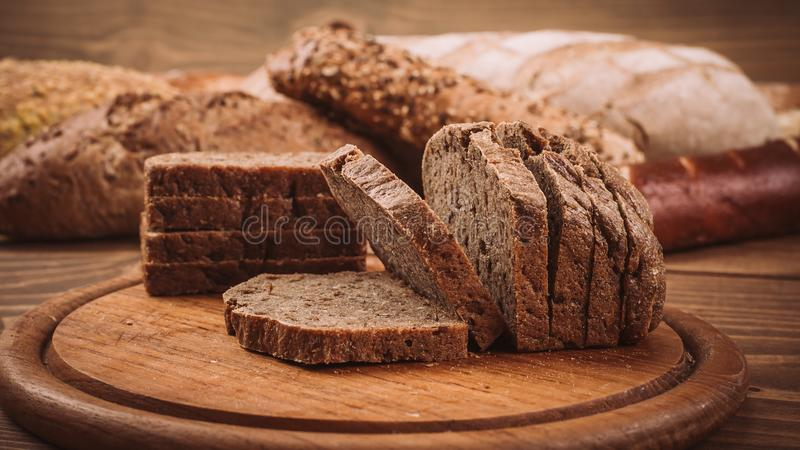 Various baked breads and rolls on rustic wooden table stock photography