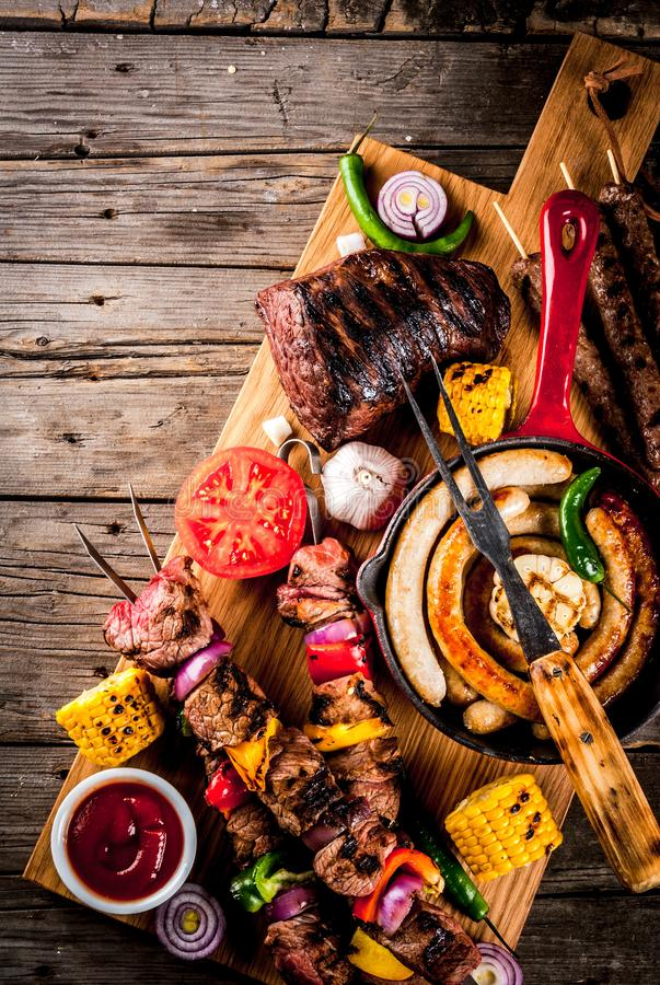 Various barbecue grill food. Assortment various barbecue food grill meat, bbq party fest - shish kebab, sausages, grilled meat fillet, fresh vegetables, sauces royalty free stock photography