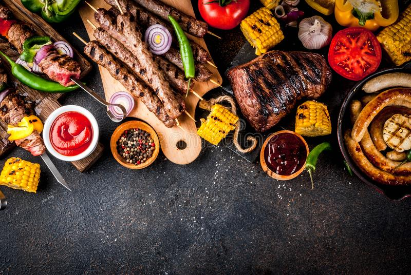 Various barbecue grill food. Assortment various barbecue food grill meat, bbq party fest - shish kebab, sausages, grilled meat fillet, fresh vegetables, sauces stock photography