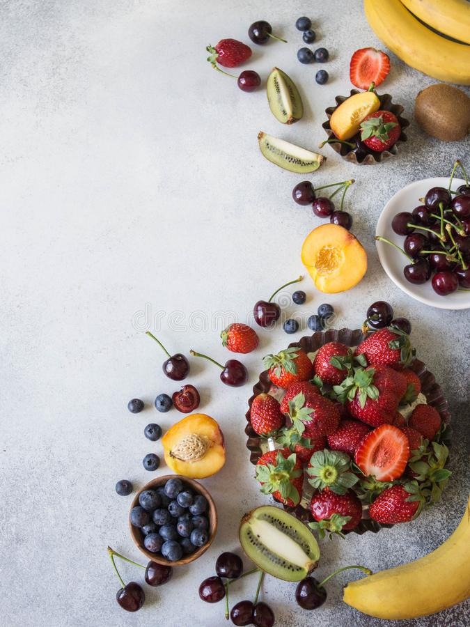 Various berries and fruits on a gray background. Strawberries, cherries, kiwi, peach, blueberries and bananas. Top view stock image