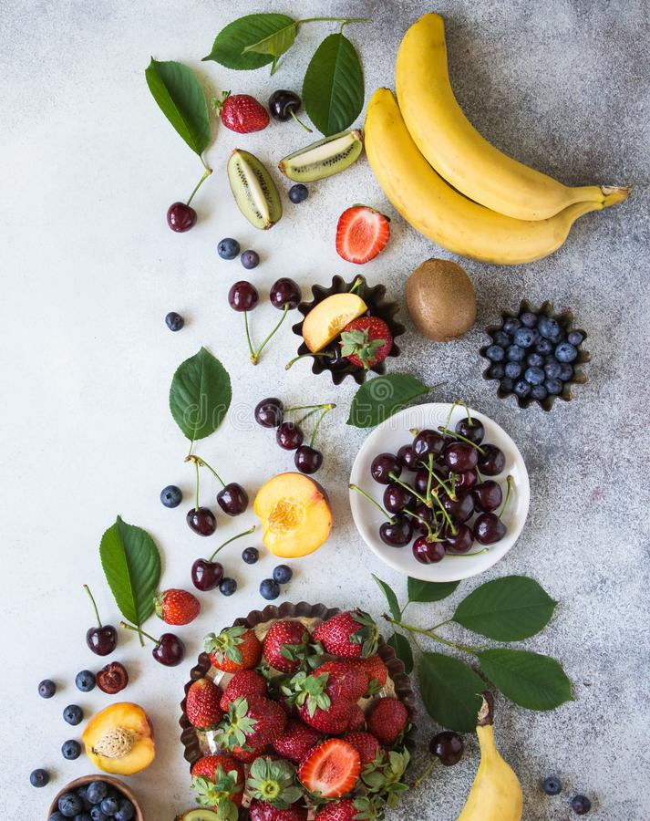 Various berries and fruits on a gray background. Strawberries, cherries, kiwi, peach, blueberries and bananas. Top view stock photos