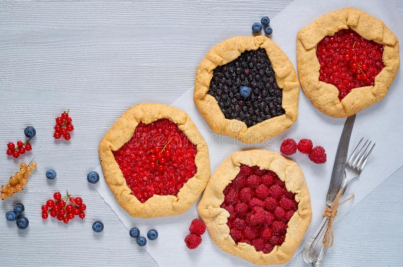 Various berries galette with knife and fork on the gray background. Vegetarian healthy tarts with fresh blueberries, raspberries royalty free stock image