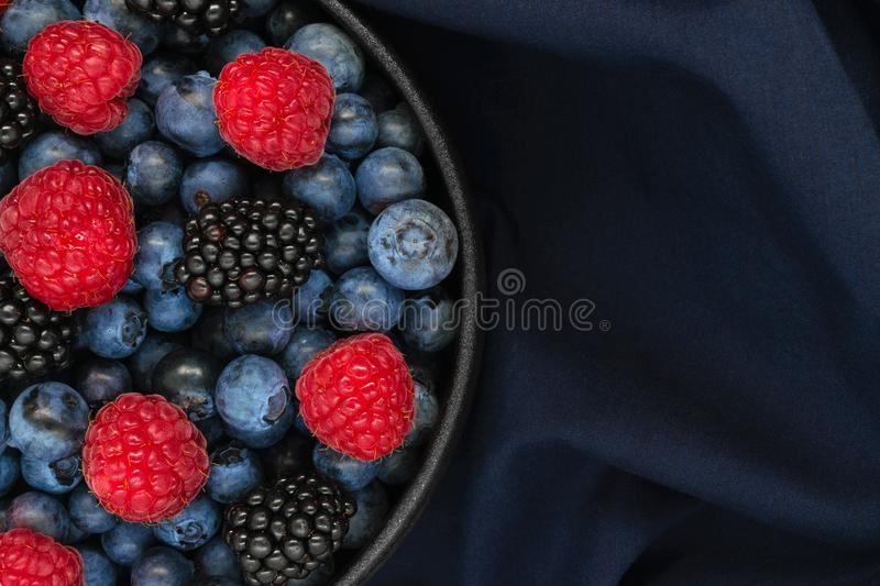 Various berries in round and black cast iron bowl stock photo