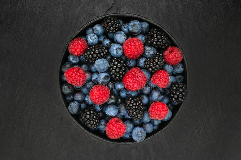 Various berries in round and black cast iron bowl stock images