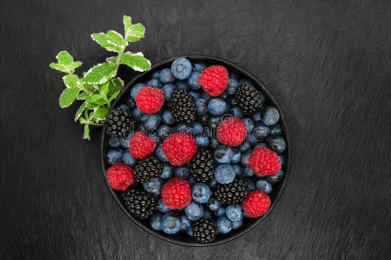 Various berries in round and black cast iron bowl stock photography