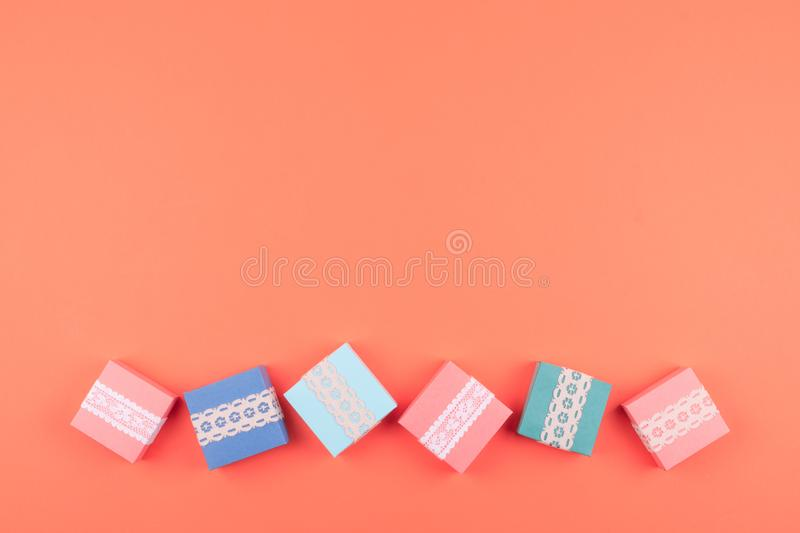 Various birthday gift boxes with lace on coral color background. Minimal concept, flat lay stock image