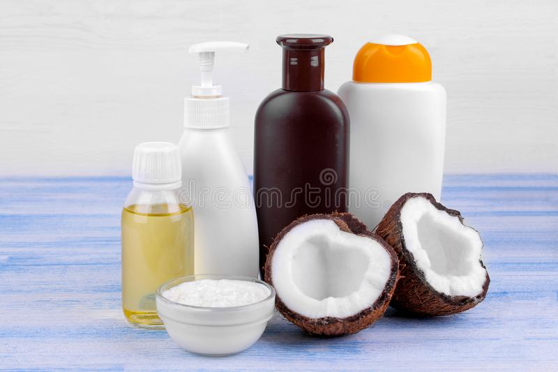 Various bottles of cosmetics with coconut extract next to fresh coconut on a blue table on a white background. Various bottles of cosmetics with coconut extract stock photography
