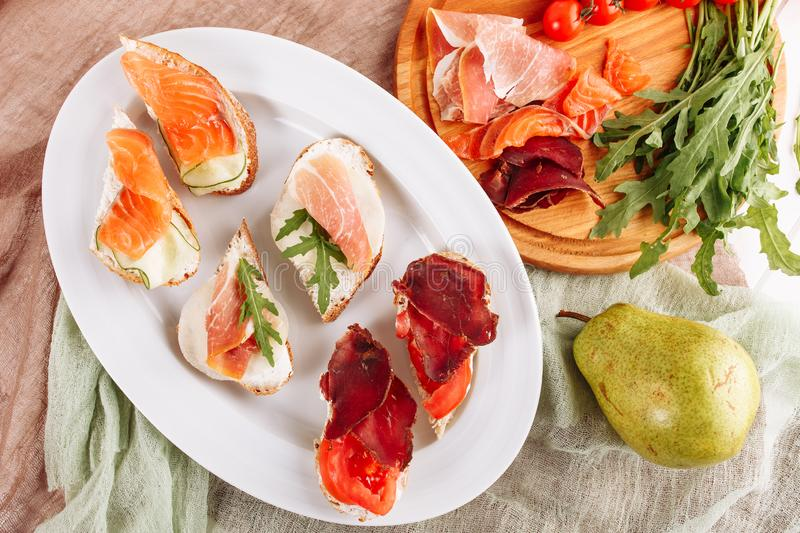 Various Bread Ham Canape Snack Top Down Flat Lay. Pork Dried Prosciutto and Salmon Sliced Meat on Italian Small Sandwich Appetizer. Tasty Jamon on White Plate royalty free stock photos