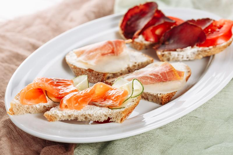 Various Bread Salmon Canape Snack Side Closeup. Pork Ham and Prosciutto Dried Sliced Meat on Italian Small Sandwich Appetizer. Tasty Jamon on White Plate stock photo