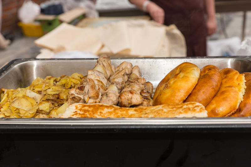 Various breads and vegetables in serving pan. Close up on various fried and baked meats neatly arranged in single stainless steel serving pan royalty free stock photography