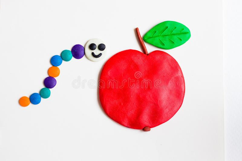 The various bright colors of the caterpillar with a joyful smile which is made of plasticine, sits next to a large red apple. She wants to eat an apple or at royalty free stock images