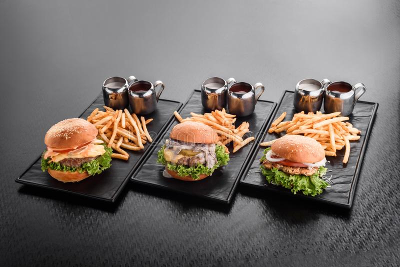 Various burgers with french fries hamburgers on plate stock photography