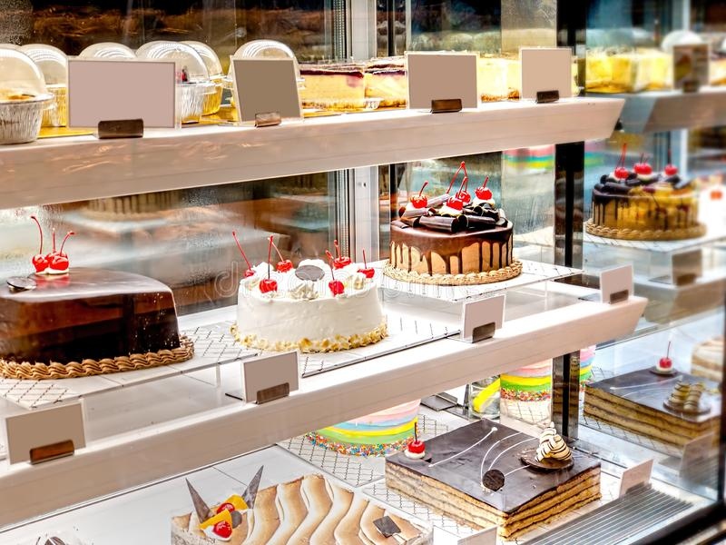 Various Cake with Icing in Refrigerated Bakery Case Cabinet. Chocolate and Cherry Tart Toping on Fridge Display stock photography