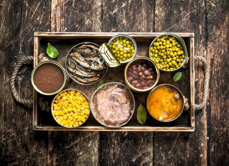 Various canned fruits, vegetables, fish and meat in tin cans on old tray. On a wooden background stock image