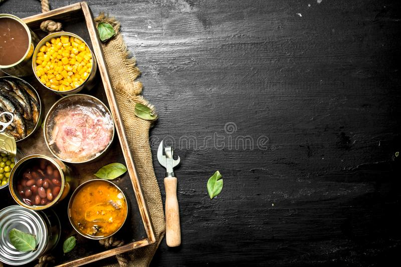 Various canned fruits, vegetables, fish and meat in tin cans on old tray. On the black chalkboard royalty free stock photos